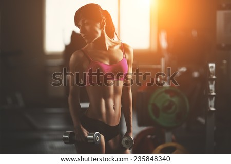 Brutal athletic woman pumping up muscles with dumbbells. Brunette sexy fitness girl in pink sport wear with perfect body in the gym posing before training set. Attractive fitness woman