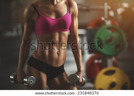 Brutal athletic woman pumping up muscles with dumbbells. Part of body. Attractive fitness woman, trained female body, lifestyle portrait, caucasian model