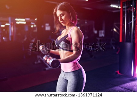 Brutal athletic woman pumping up muscules with dumbbells. #1361971124