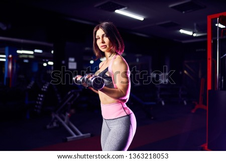 Brutal athletic woman pumping up muscules with dumbbells. #1363218053