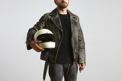 Brutal attractive bearded guy in worn oversized vintage motorcycle leather jacket and classic helmet in hand poses in black blank t-shirt from premium thin cotton, isolated on white mockup