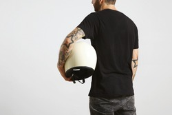 Brutal attractive bearded guy with tattooed hands poses backside in black blank t-shirt from premium thin cotton and holds ivory classic biker helmet, isolated on white mockup