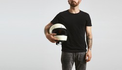Brutal attractive bearded guy with tattooed hands poses in black blank t-shirt from premium thin cotton and holds ivory classic biker helmet, isolated on white mockup