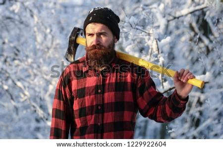 Brutal bearded lumberjack with ax in winter forest. Lumberjack with an ax in his hands. Male holds an ax on a shoulder. Brutal bearded man. Handsome man, hipster in snowy forest. Bearded lumberjack.