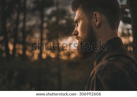 Brutal bearded man confidently looking forward. Standing alone in forest outdoor with sunset nature on background