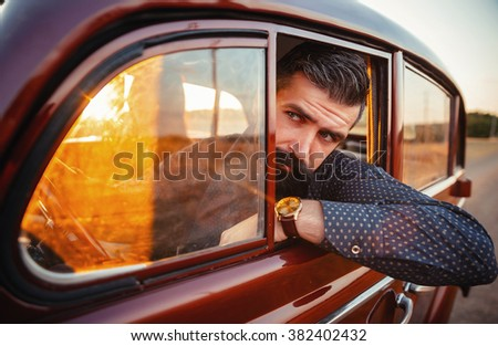 brutal bearded man with a mustache in a shirt, pants with suspenders with a girl with dark hair and big lips with bright red lipstick in a short dress and heels near retro car at sunset
