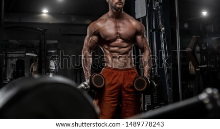Brutal handsome Caucasian bodybuilder working out training in the gym gaining weight pumping up muscles and poses fitness and bodybuilding concept