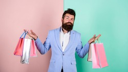brutal hipster shopper. big sale. male shopaholic hold shopping bags. present packages for holiday preparation. special offer on black friday. shop closeout. rich businessman with purchase.