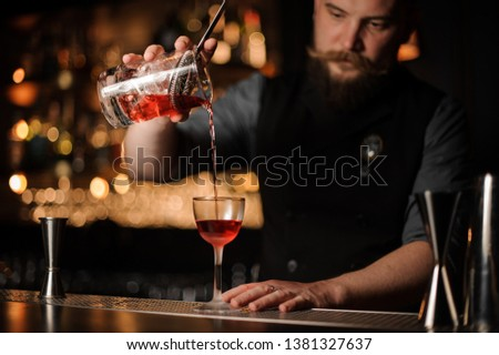 Brutal male bartender pours an alcohol drink with metal strainer #1381327637