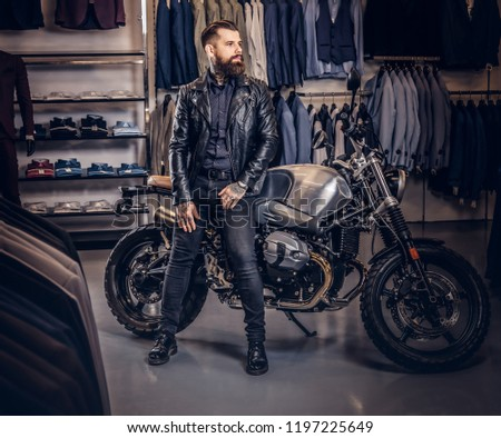 Brutal male dressed in black jacket leaning on a retro sports motorbike at the men's clothing store. #1197225649