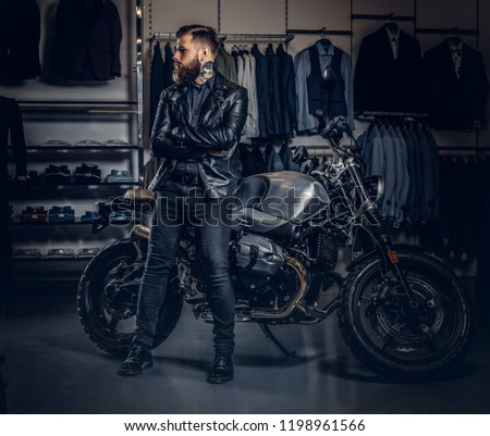 Brutal male dressed in black jacket posing with crossed arms near retro sports motorbike at the men's clothing store. #1198961566