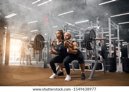 Brutal male weightlifter standing behind young sporty woman backing up squatting process with heavy barbell in brightly lighted gym, practicing in white smoke, shot from below, indoor shot