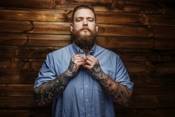 Brutal male with beard and tatooes buttons up his t-shirt
