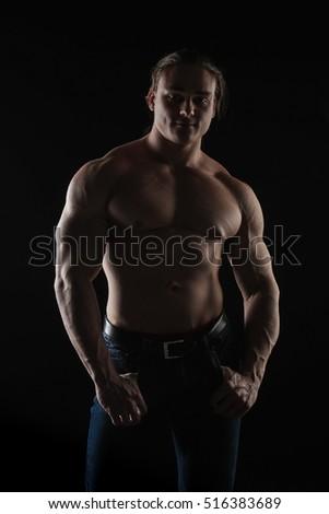 Brutal man bodybuilder athlete on a black background. #516383689