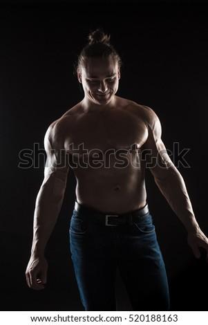 Brutal man bodybuilder athlete with long hair on a black background. #520188163