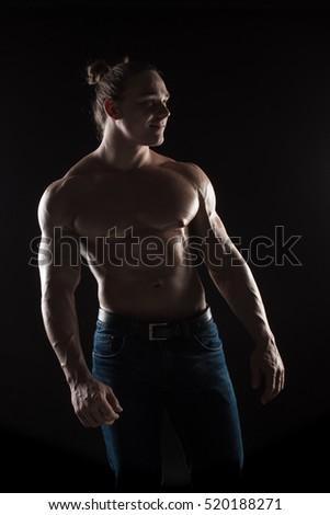 Brutal man bodybuilder athlete with long hair on a black background. #520188271
