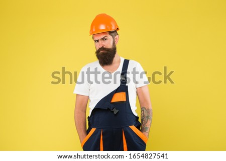 Brutal man builder. Engineer builder in uniform. Man builder hard hat. Renovating home opportunity to refresh expand and renew. Craftsman keep head safe in helmet. Building improvement and renovation.