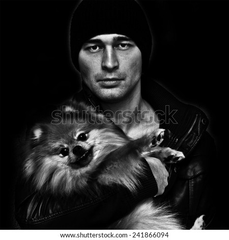 Brutal man in a hat and leather jacket with a dog in her arms on a black background