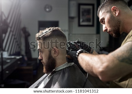 Brutal man sits in the chair at a barber shop. Barber in black gloves shaves man's hairs at the back.