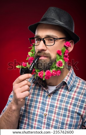Brutal man with flowers in his beard, in hat and with pipe is standing against red background.
