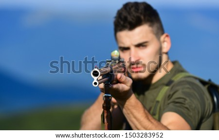 Brutal masculine hobby. Man observing nature background. Hunter hold rifle. Hunter handsome guy with weapon. Safety measures. Natural environment. Hunter spend leisure hunting. Hunting equipment.