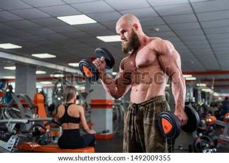 Brutal, muscular, bald with a beard athlete in the gym. Lifts heavy weights, trains the biceps. Beautiful chest muscles