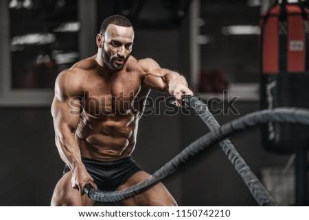 Brutal strong bodybuilder athletic man pumping up muscles workout bodybuilding concept background - muscular bodybuilder handsome men doing exercises in gym naked torso sport and diet concept