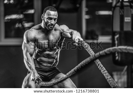 Brutal strong bodybuilder athletic man pumping up muscles workout bodybuilding concept background - muscular bodybuilder handsome men doing exercises in gym naked torso sport and diet concept