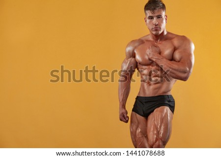 Brutal strong muscular bodybuilder athlete man pumping up muscles on yellow background. Workout bodybuilding concept.