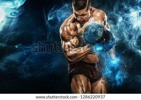 Brutal strong muscular bodybuilder athletic man pumping up muscles with dumbbell on black background. Workout bodybuilding concept. Copy space for sport nutrition ads.