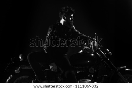 Brutality and masculine concept. Macho, brutal biker in leather jacket stand near motorcycle at night time. Man with beard, biker in leather jacket lean on motor bike in darkness, black background. #1111069832