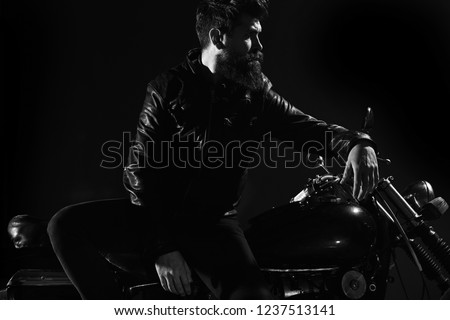 Brutality and masculine concept. Man with beard, biker in leather jacket lean on motor bike in darkness, black background. Macho, brutal biker in leather jacket stand near motorcycle at night time. #1237513141