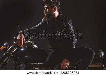 Brutality and masculine concept. Man with beard, biker in leather jacket lean on motor bike in darkness, black background. Macho, brutal biker in leather jacket stand near motorcycle at night time. #1288308298