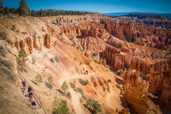 Bryce Canyon with red hoodoo rock formations viewed from above with hikers wandering around the bottom
