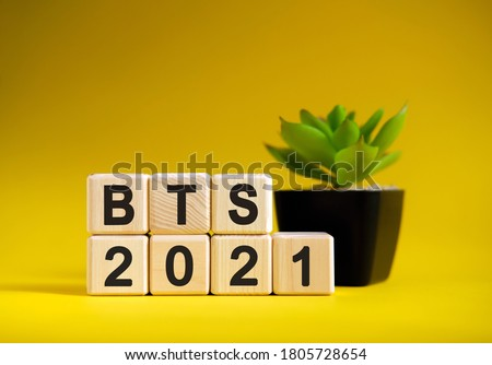 BTS - business financial concept on a yellow background. Wooden cubes and flower in a pot. Stock fotó ©