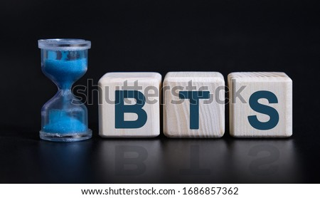 BTS concept with an hourglass. Wooden cubes on a black table Stock fotó ©