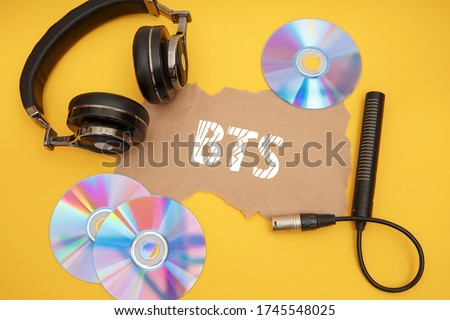 BTS concept with headphones and music discs on a yellow background. Stock fotó ©