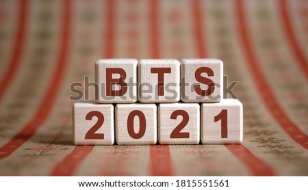 BTS 2021 text on wooden cubes on a monochrome background with reflection. Stock fotó ©