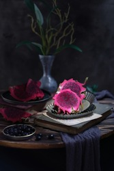 Buah Naga or Dragon Fruit or pitaya and small tree on table.  Buah naga is rich in flavonoids and antioxidants, source of vitamin C. It can be eaten directly or can be made juice.