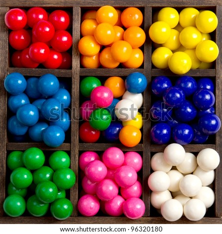 Bubble gum sorted into colors in a printers box 8 different colors