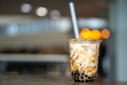 Bubble milk tea in take away glass on the wood table with space for textures