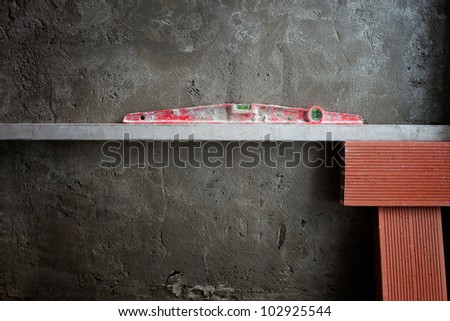 bubble spirit level tool in red on costruction cement wall with bricks