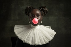 Bubbles gum. Medieval African young woman in black vintage dress with big white collar isolated on dark green background. Concept of comparison of eras, modernity and renaissance. White pearls