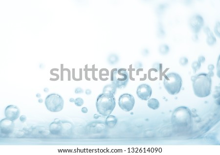 Bubbles of oxygen in glass of water on a blue background. Mineral water. Water enriched with oxygen.Oxygen. Water.Water background. Macro.Texture.Glass with water.Natural.Background.Neutral background