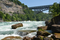 Bubbling rapids of the Niagara River flow over stones and rocks with bridge, forest and rock face in the background in sunny weather