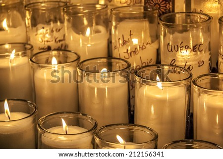 Buch of big candles burning at a catholic church symbolizing religion and God Fearing.