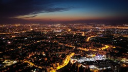 Bucharest city drone view at sunset, with illuminated streets and traffic lights