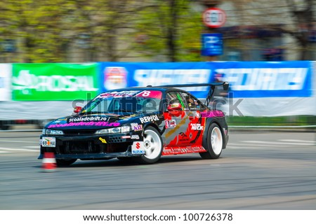 BUCHAREST, ROMANIA - APRIL 08: Unknown car driver piloting his car at Romania's National Championship Drift 2012 in front of Parliament House on April 08, 2012, Bucharest, Romania