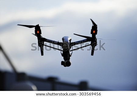 BUCHAREST/ROMANIA - AUGUST 1: Aerial filming drone in action, silhouetted against blue sky, on August 1, 2015 in Bucharest.
