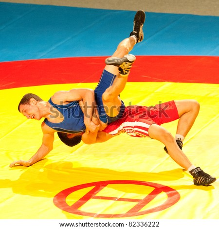 BUCHAREST, ROMANIA - JULY 25: Unidentified wrestlers fight during Junior Wrestling World Championship on July 25, 2011, Bucharest, Romania